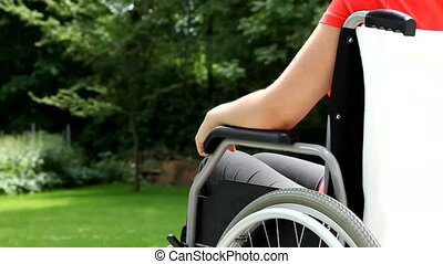 Young woman on wheelchair in garden