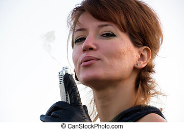 Young woman on white background holding a gun with a smoking gun