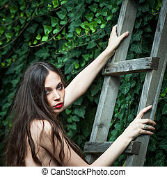 young woman on wooden ladders lean on wall covered with climber plant