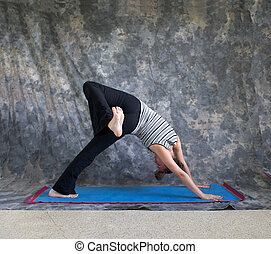 Young woman on yoga mat  doing Yoga posture Eka Pada Adho Mukha Svanasana or one leg down dog pose against a grey background in profile, facing right lit by diffused sunlight.