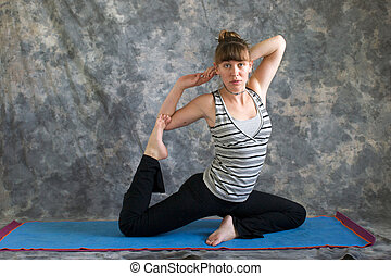 Young woman on yoga mat  doing Yoga posture Kapotasana or Pigeon Pose variation against a grey background in profile, facing right lit by diffused sunlight.