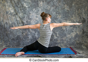 Young woman on yoga mat  doing Yoga posture Virabhadrasana II or seated warrior 2 pose from the back against a grey background in profile, facing right lit by diffused sunlight.