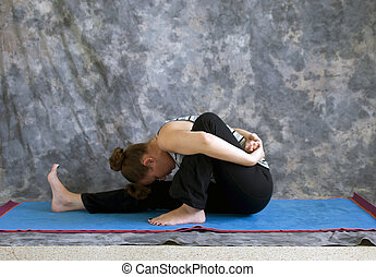 Young woman on yoga mat in woman doing Yoga posture Marichyasana I or bound forward fold pose against a grey background in profile, facing left lit by diffused sunlight.