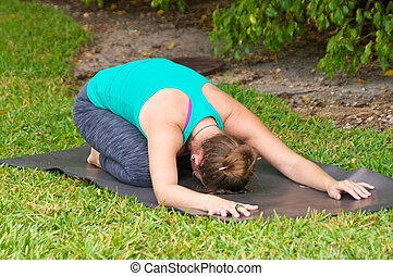 Young woman on yoga mat outdoors on the grass with trees in...