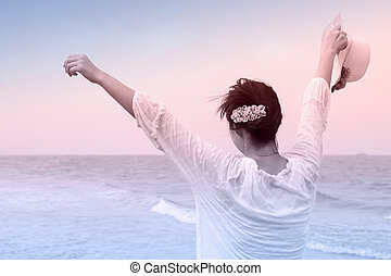 Young woman open arms and holding hat on the beach