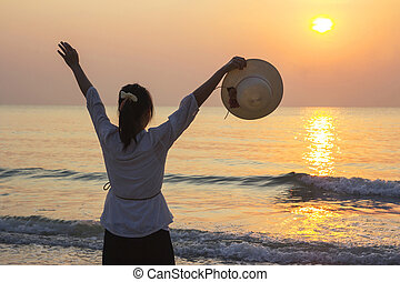 Young woman open arms and holding hat under the sunrise at beach