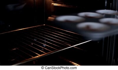 Young woman open the oven and puts on the baking dish with dough. Female cooking the cupcakes in the kitchen.