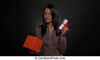 Young woman opening a gift box and getting surprised by the present