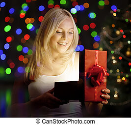 Young woman opening gift box in front of christmas tree