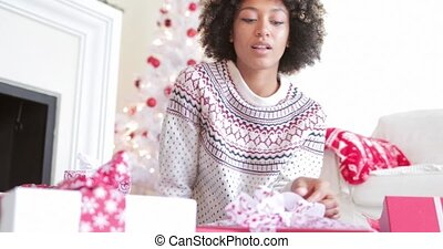 Young woman opening her Christmas gifts - Low angle view of...