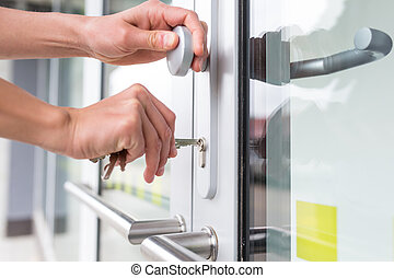 Young woman opening the front door of her apartment building