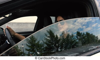 Young Woman opens a car window - Young woman opens a car...