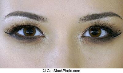 Young woman opens beautiful eyes.