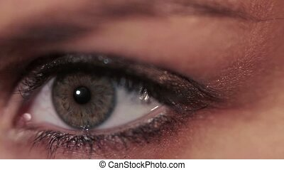 Young woman opens her eye, close-up. Look away and look into...