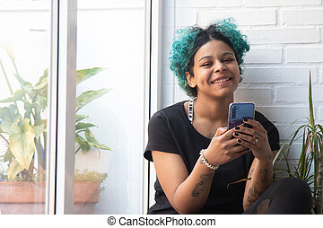 young woman or girl with smartphone at home by the window