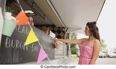 young woman ordering meal at food truck - street sale,...