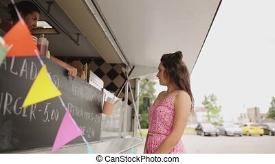 young woman ordering vegan wrap at food truck - street sale,...