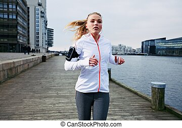 Young woman out for a jog - Fit young woman running on the...