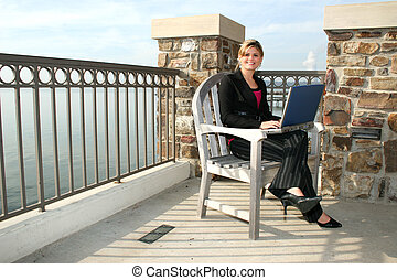 Young Woman Outdoors at the Lake with Laptop