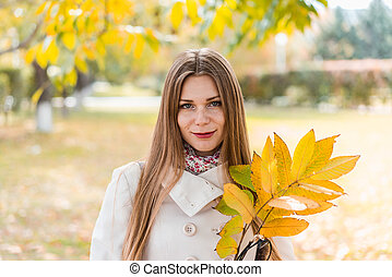 Young woman outdoors in park on sunny autumn day