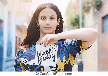 """Young woman outdoors showing a notepad with the text """"black friday"""" written in it."""