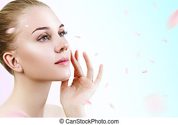 Young woman over fresh blue background with swirl petals.