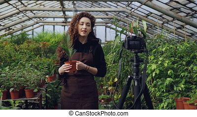 Young woman owner of hothouse is recording video about...