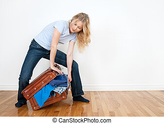 Young woman packing a suitcase