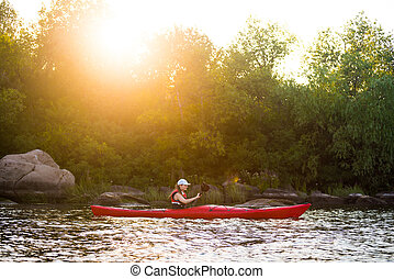 Young Woman Paddling the Red Kayak in Beautiful Lagoon with Green Trees and Stones at Warm Summer Sunset
