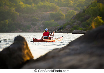 Young Woman Paddling the Red Kayak on Beautiful River or Lake in the Mountains