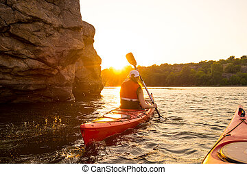 Young Woman Paddling the Red Kayak on Beautiful River or Lake near High Rocks at Sunset