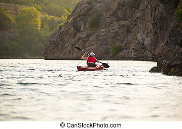 Young Woman Paddling the Red Kayak on Beautiful River or Lake near High Rocks