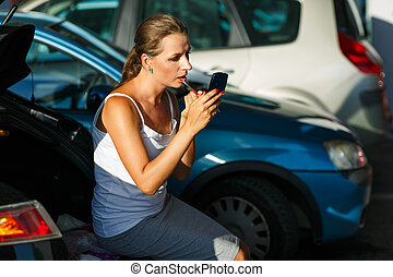 Young woman paint her lips sitting on the trunk of a car on the parking