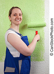 Young woman painting a wall