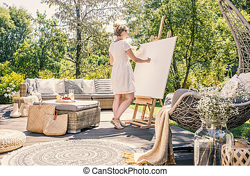 Young woman painting on a white canvas on a sunny terrace with garden furniture in the summer