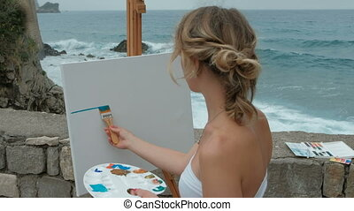 Young woman paints picture standing by seaside on summer day.