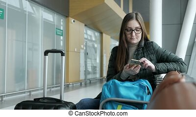 Young woman passes e-check in smartphone waiting her flight in airport.