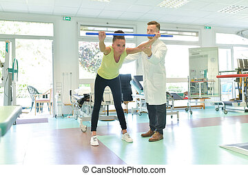 young woman patient doing physical exercises in a rehabilitation study