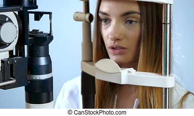 young woman patient looking at eye test machine in...