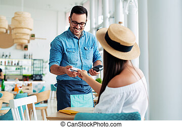 Young woman paying for cafe by credit card reader.