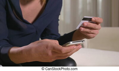 Young woman paying with credit card on a smart phone