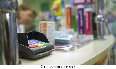 Young woman paying with her credit card in a drugstore close up video