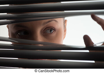 young woman peeking through closed blinds or shutters. Woman...