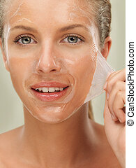 closeup beauty portrait of beautiful blonde woman peeling off a facial mask, smiling