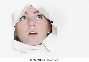 young woman peeping through hole in paper
