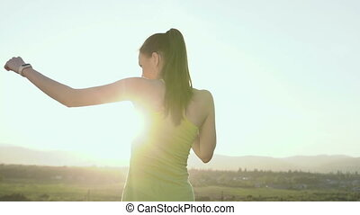 Young woman perform boxing with shadow on the top of mountain at sunset . Sports girl engaged in melee combat, sports boxing at sunset. Boxing training in the outdoor