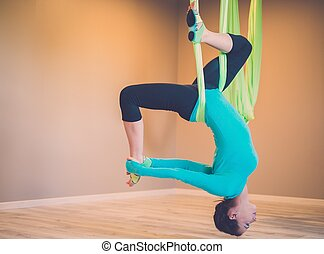 Young woman performing antigravity yoga exercise
