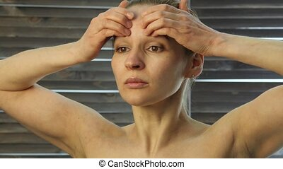 young woman performs anti-aging exercises. face fitness