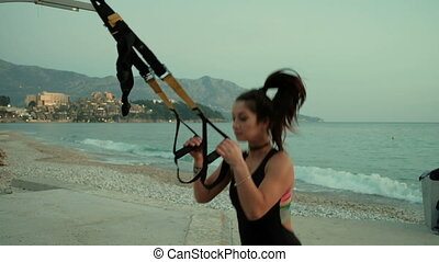 Young woman performs jumping sports belts Total Resistance eXercise.