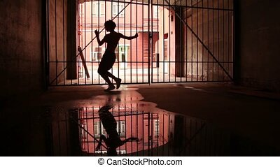 Young woman performs modern dance near lattice gate in dark...